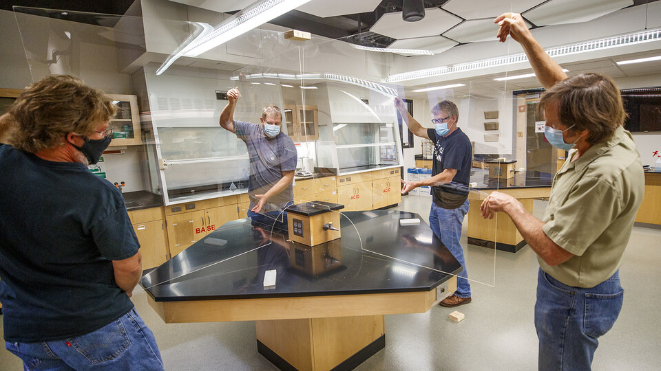 Department staff and faculty installing plexiglas in chemistry laboratories.